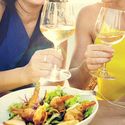 Two women enjoying food and a glass of wine